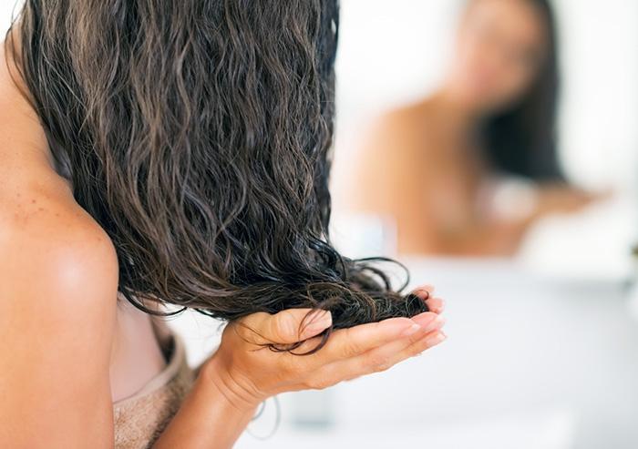 наносит маску на волосы